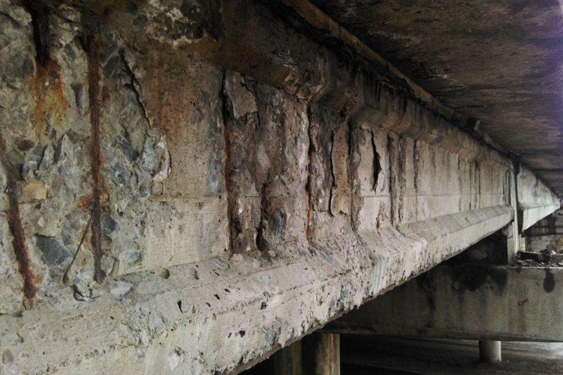 Разрушение поверхностного слоя бетона пролетной балки с оголением арматуры
